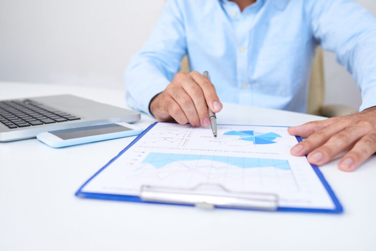 Close-up image of business executive analyzing diagram in financial report with sales data