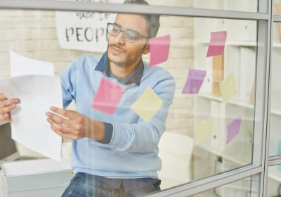 Portrait of young Middle-Eastern entrepreneur sticking post it notes on glass wall while planning startup project in modern office, shot from behind  glass wall